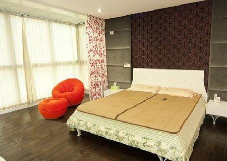 独特花纹的深褐色软包背景墙与淡颜色的床